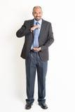 Full length mature Indian businessman holding something Stock Photos