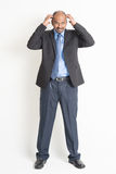 Full length mature Indian businessman scratching head Royalty Free Stock Image