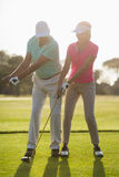 Full length of mature male golf player teaching woman. Full length of mature male golf player teaching women while standing on field Royalty Free Stock Photos