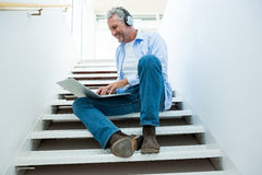 Full length of mature man using laptop. On steps at home Stock Image