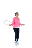 Full length of mature woman exercising with jump rope Royalty Free Stock Photo
