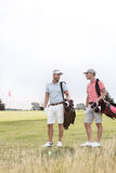 Full-length of men conversing at golf course against clear sky Royalty Free Stock Images