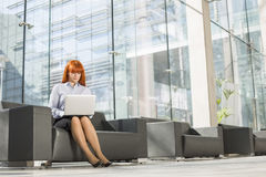 Full-length of middle-aged businesswoman using laptop at office lobby Stock Photos