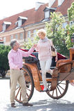 Full-length of middle-aged man assisting woman out of horse cart Stock Image