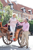 Full-length of middle-aged man assisting woman out of horse cart Stock Images
