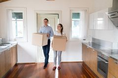 Wife and husband holds carton boxes standing in the kitchen. Full length millennial wife and husband hold carton boxes with belongings standing in modern kitchen stock images