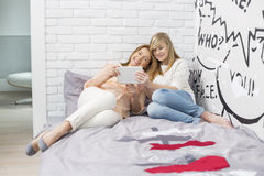 Full-length of mother with daughter using tablet PC in bedroom Royalty Free Stock Photos