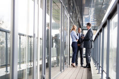 Full length of multi-ethnic business people discussing on office balcony Royalty Free Stock Image