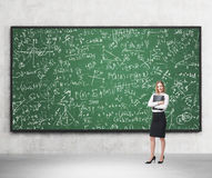 Full length of nice lady who holds black folder and stands in front of the green chalkboard. Royalty Free Stock Images