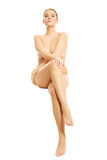 Full length nude woman sitting with crossed hands Royalty Free Stock Photo