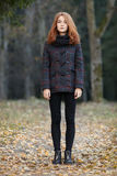Full length outdoors portrait of young beautiful redhead woman in scarf, jacket, black jeans and boots standing on a forest path Stock Photos