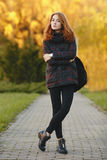 Full length outdoors portrait of young beautiful redhead woman in scarf, jacket, black jeans and boots standing on a park path Stock Images