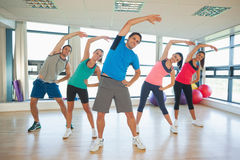 Full length of people doing power fitness exercise at yoga class Stock Photography