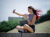 A pretty teenage girl making a selfie-portrait on a park background. Outdoors, walks concept. Copy space. stock photography