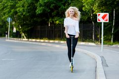 Full-length photo of curly-haired athletic woman kicking on scooter in park royalty free stock photography