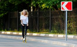 Full-length photo of curly-haired athletic woman kicking on scooter in park stock images