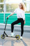 Full-length photo of curly-haired athletic woman kicking on scooter in park stock photo
