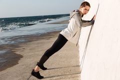 Full-length photo of fit girl doing push-ups while standing nea. R white wall, looking at camera, seaside outdoor stock photography