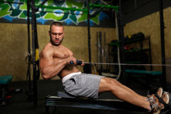 A photo of a beautiful man with a perfect body doing sporty exercises on a gym background. Fitness and sports concept. Royalty Free Stock Images