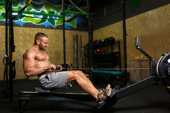 A photo of a beautiful man with a perfect body doing sporty exercises on a gym background. Fitness and sports concept. Royalty Free Stock Photography