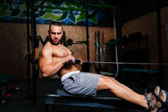 A photo of a charming man with a perfect body doing sporty exercises on a gym background. Fitness and sports concept. Stock Image