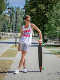A fashionable young hipster man with a skateboard on a blurred natural background. Healthy and active lifestyle. Stock Images