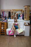 A full-length photo of a tired young woman holding her purchases and sitting on the clothing store background. Copy Stock Photography