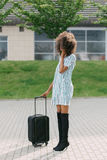 Full-length photo of the well-dressed afro-american woman holding the luggage while talking via the mobile phone. Stock Images
