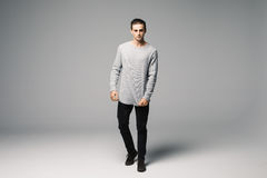 Full length photo of a young fashion man with his hands folded, looking into the camera and smiling.on gray background. Full length photo of a young casual man Stock Photo
