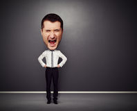 Full-length picture of angry businessman. With big head over dark background Royalty Free Stock Image