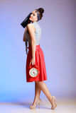 Full length pin-up girl woman with clock going on a date. Full length of fashionable pin-up girl young woman with red clock and handbag going on a date on stock image
