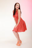 Full length pinup girl brunette woman in retro red dress winking. Stock Photography