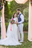 Full-length portait of just married couple. New husband and wife posing under textile arch at their wedding ceremony in the park with pink accessories Royalty Free Stock Image