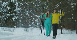 Full length portrait of active young couple enjoying skiing in snowy winter forest, focus on smiling woman in front stock video footage