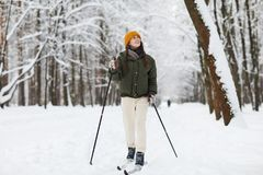 Cheerful Woman Skiing in Forest. Full length portrait of active young woman skiing alone in beautiful winter forest enjoying nature, copy space royalty free stock photo