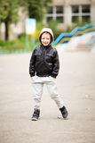Full-length portrait of adorable little boy wearing black leather jacket. Urban kids. Hands in pockets. Loss of primary teeth in children stock photos
