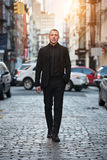 Full-length portrait of adult businessman walking on city street wearing black suit.  royalty free stock images