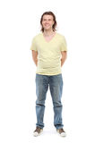 Full length portrait of adult man. Over 30 years with hair to shoulders in a shirt, jeans and sneakers with a little paunch, which has removed hands behind back Royalty Free Stock Images