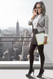 Full length portrait of an african american business woman. A full length portrait of an african american business woman smiling on phone Stock Photo