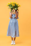 Full-length portrait of african woman hiding behind bouquet flow Stock Image