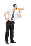 Full length portrait of an angry businessman shouting via megaphone. Isolated on white background stock images