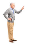 Full length portrait of an angry mature man pointing with finger. And threatening isolated on white background royalty free stock image
