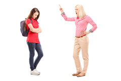Full length portrait of an angry mother shouting at her daughter. Isolated on white background royalty free stock images