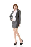 Full length portrait of Asian business woman. Wear skirt suit, isolated on white background stock image