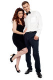 Full length portrait of attractive couple. Dressed in party wear attire. Isolated against white Stock Photo