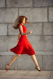 Full length portrait of attractive elegant young woman in red dress. Full length portrait of attractive elegant young woman in a red dress, jumping on the Royalty Free Stock Photo