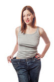 Full-length portrait of attractive slim european young smiling woman in big jeans showing successful weight loss with her happy fa Royalty Free Stock Photo