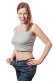 Full-length portrait of attractive slim european young smiling woman in big jeans showing successful weight loss with her happy fa Royalty Free Stock Photography