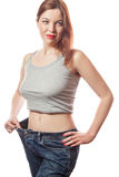 Full-length portrait of attractive slim european young smiling woman in big jeans showing successful weight loss with her happy fa Stock Photo