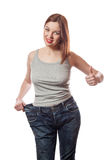 Full-length portrait of attractive slim young smiling woman in big jeans showing successful weight loss with her thumb up, isolate Royalty Free Stock Image